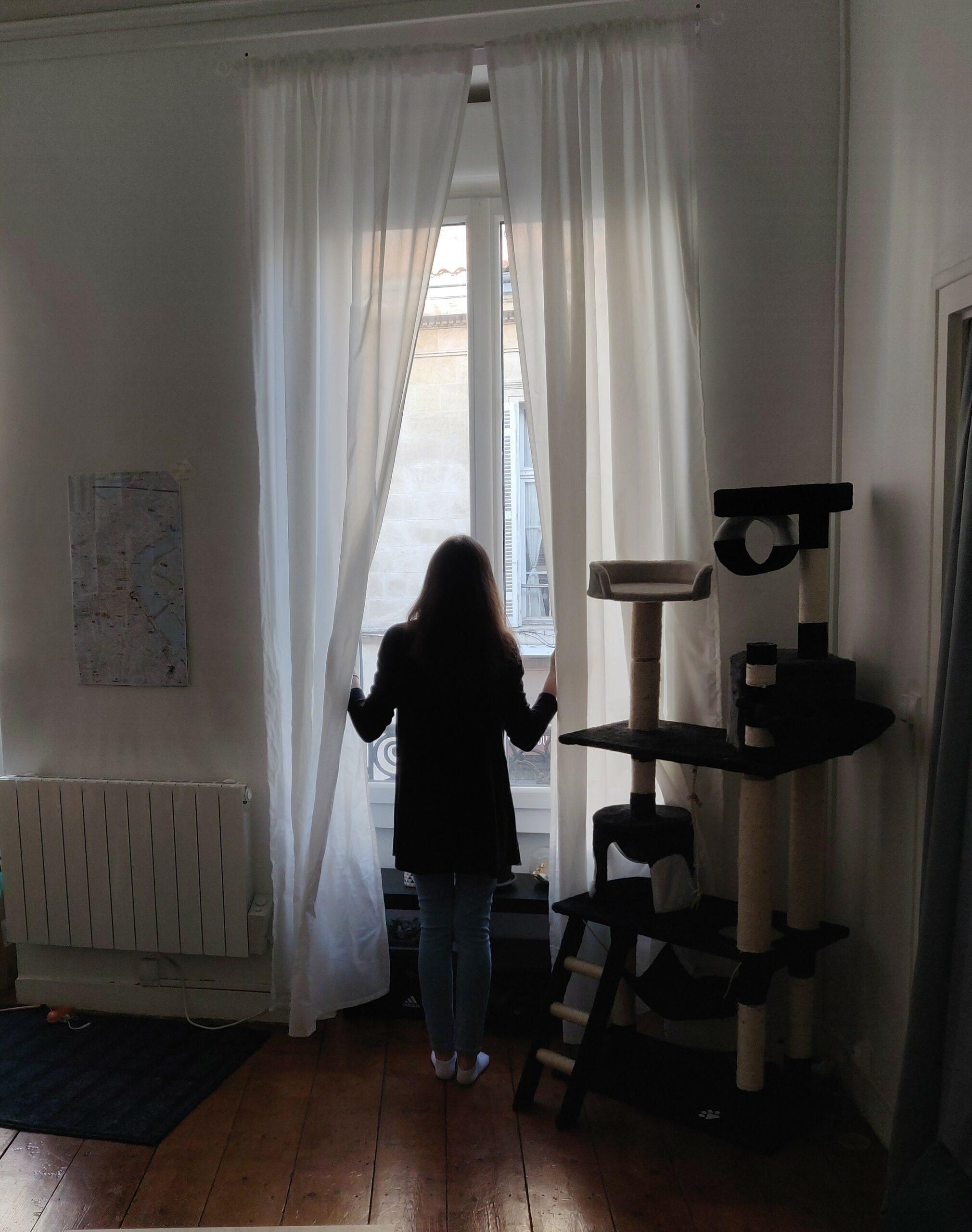 Plan d'ensemble sur la scène. Une femme, habillée en jean, chaussettes blanche et gilet noir ouvre les rideaux pour regarder dehors. On voit a sa droite, un arbre à chat noir et beige, qui est plus grand qu'elle. A gauche est présent un radiateur blanc et un tapis bleu. Une carte de Bordeaux est accrochée au dessus du radiateur.