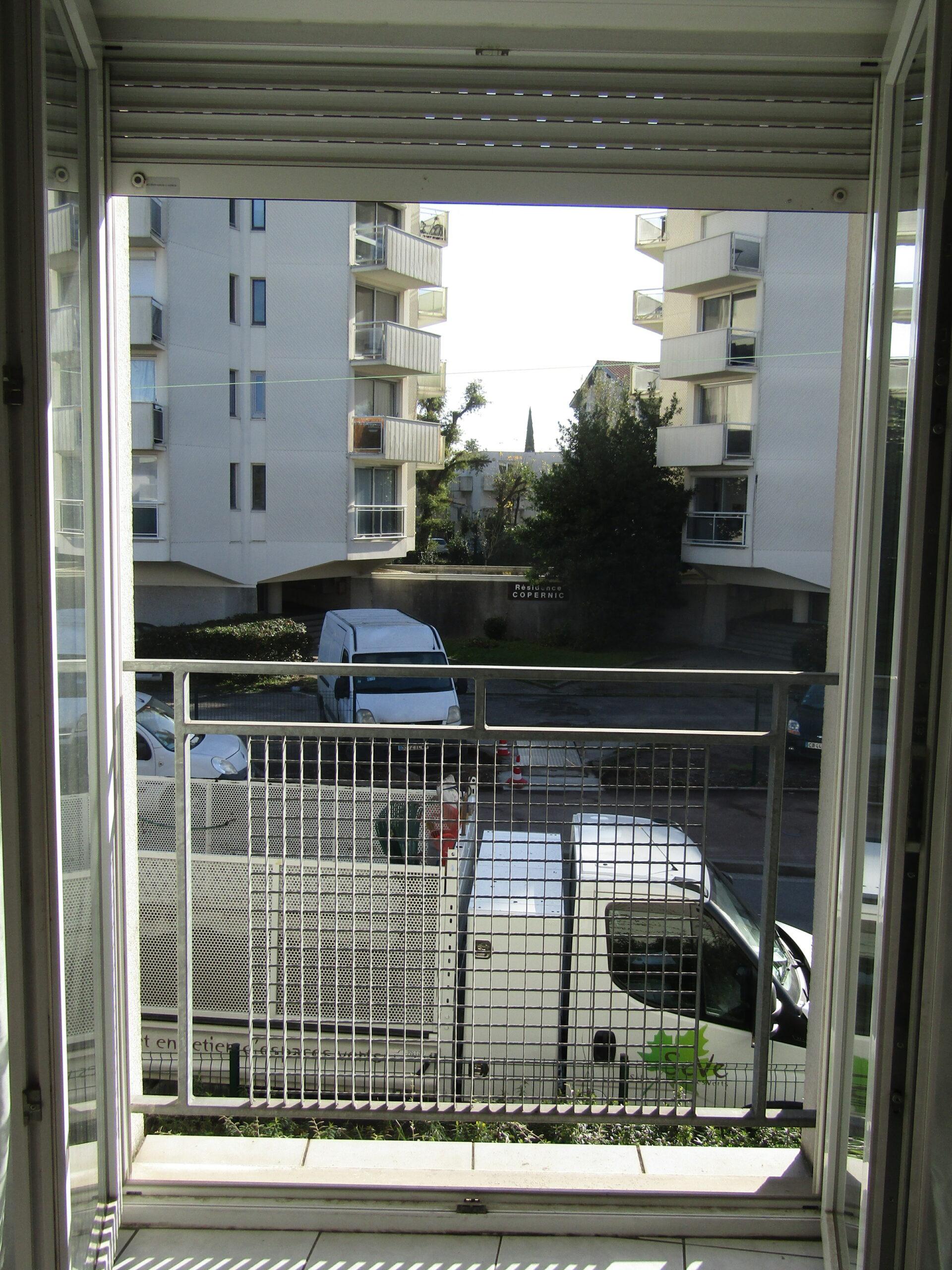 Une fenêtre ouverte qui donne sur l'extérieur, on peut apercevoir une grille sur le rebord de la fenêtre. À l'extérieur on voit un camion et des bâtiments.