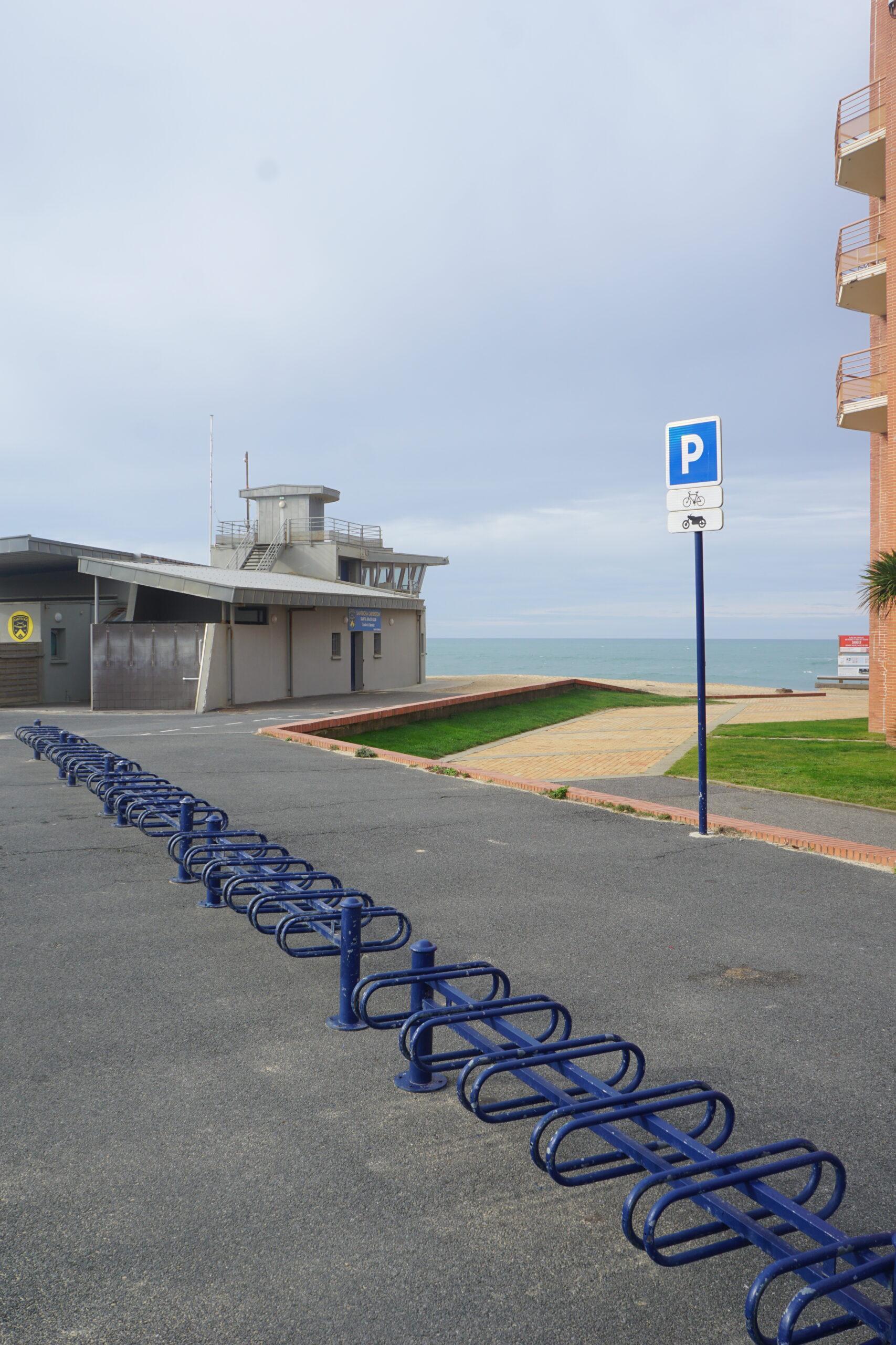 Photographie d'un parc à vélo vide en bord de mer.