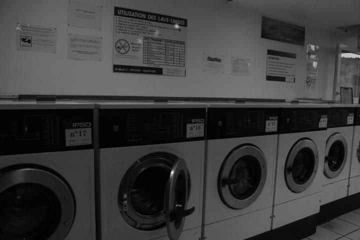 L'intérieur d'une laverie avec plusieurs machine à laver dont une ouverte et trois fermées. Il y a aussi un panneau d'instructions pour l'utilisation des machines. L'image est en noir et blanc.