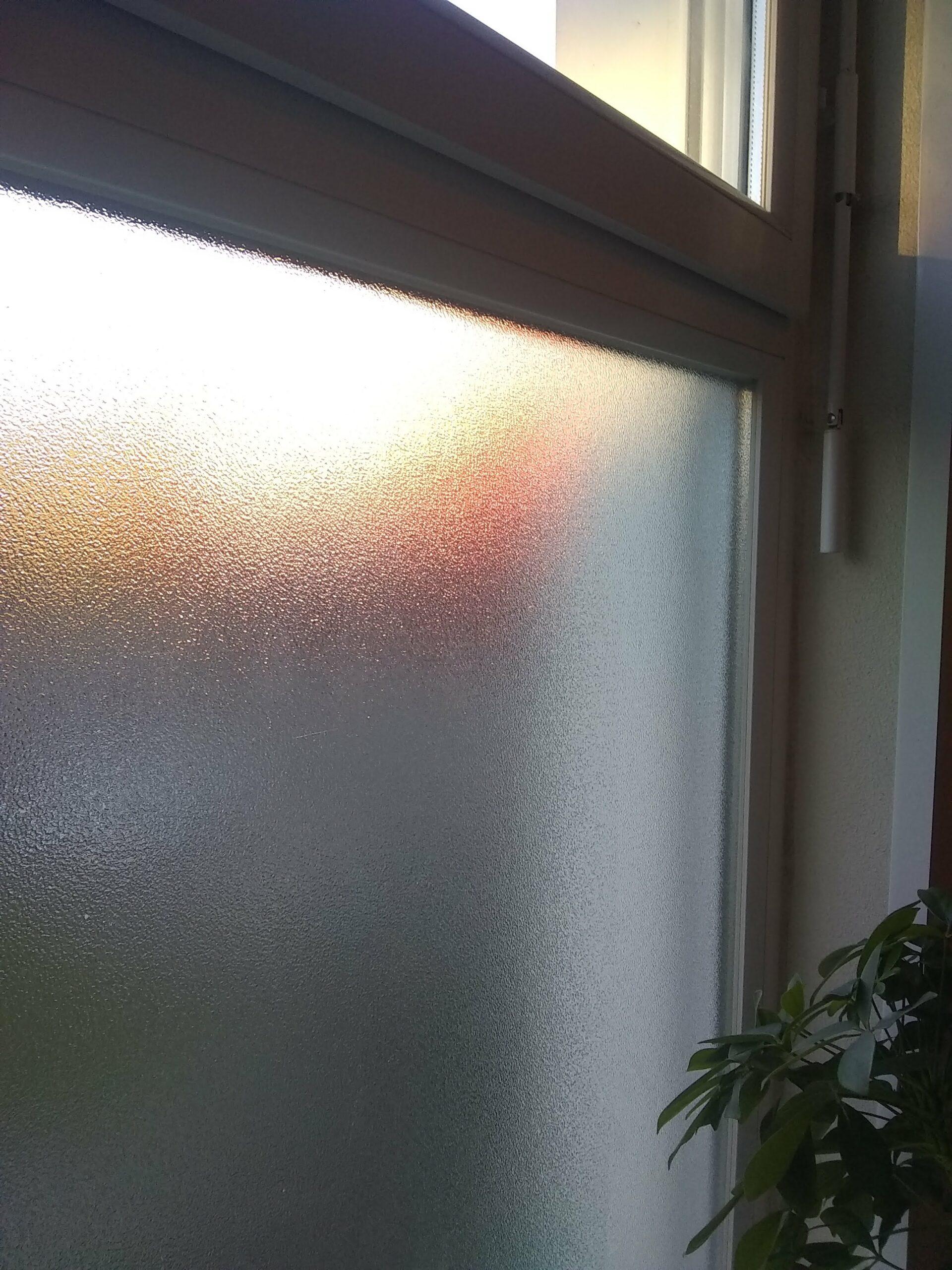 Fenêtre texturée de l'appartement, vue sur le couché de soleil