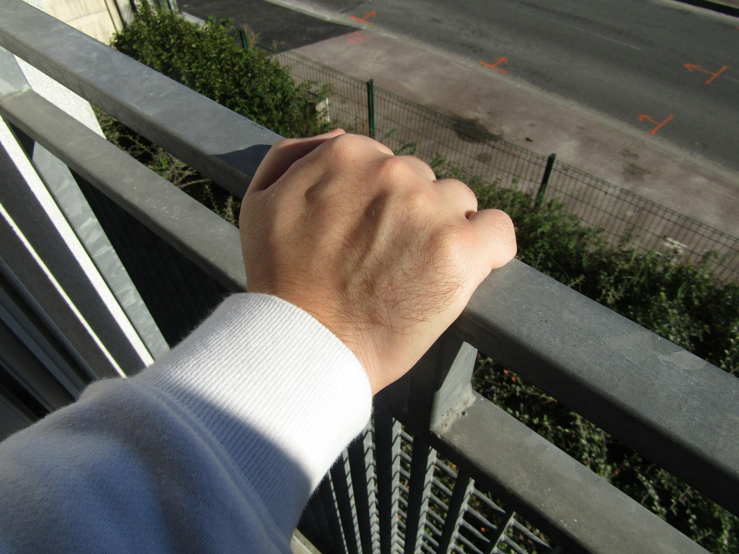Une main seule posée sur une rembarde. On peut apercevoir en dessous un jardinet avec quelques plantes, un trottoir et une route.