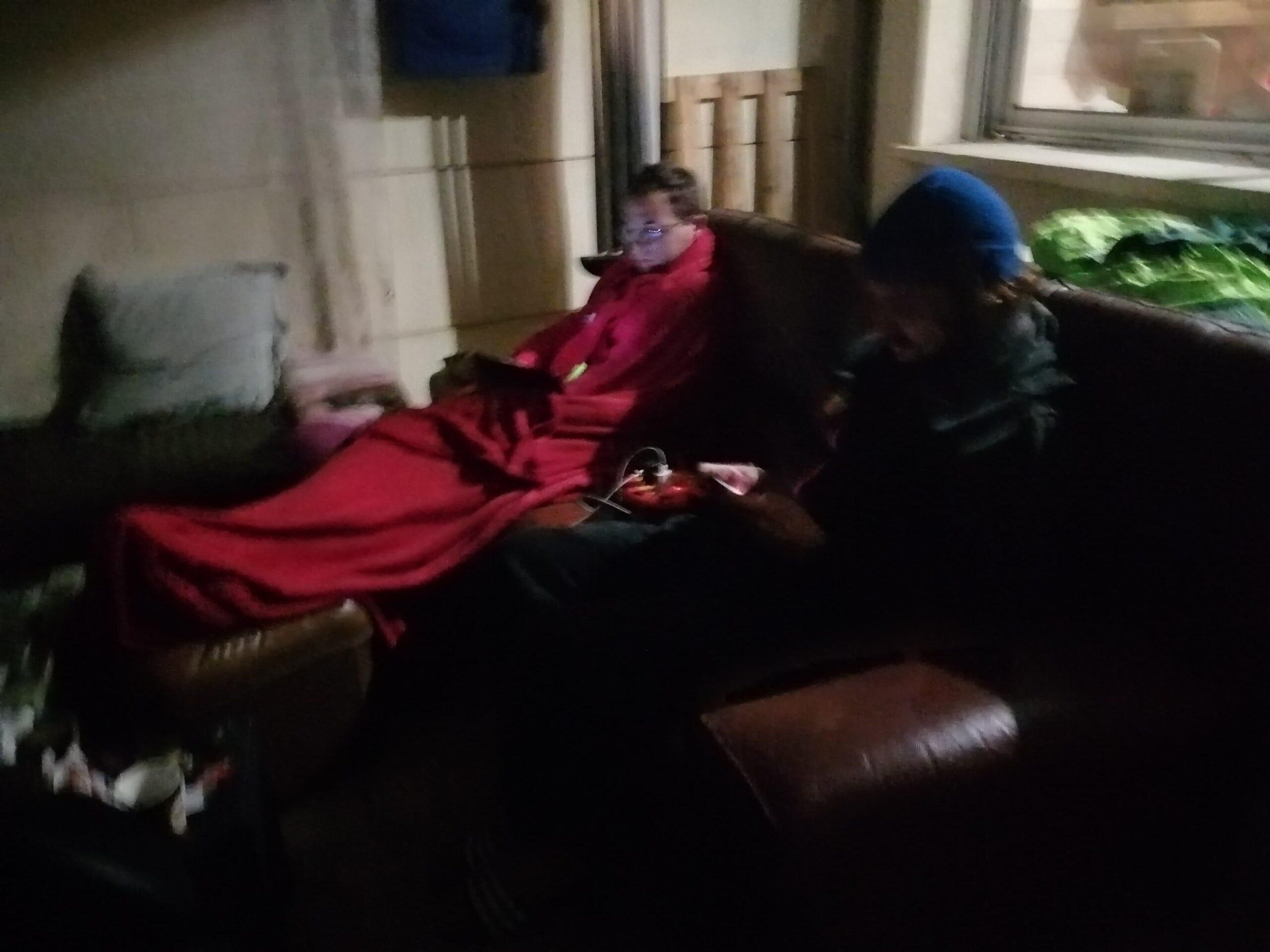 Dans une ambiance sombre, à la nuit tombée, deux jeunes hommes occupés sur leurs téléphones portables sont assis sur un canapé marron. Ils sont juste séparés par une rallonge multiprise, mais ne se parlent pas. Ils sont bien trop occupés sur leurs téléphones respectifs.
