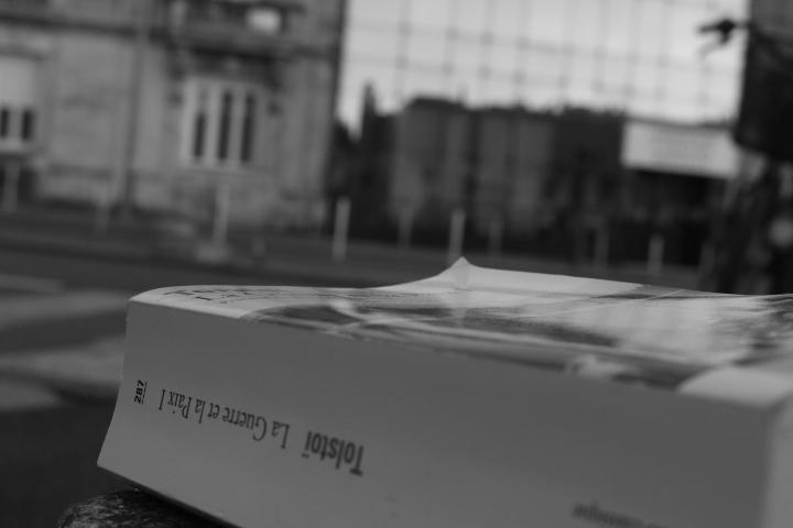 Un livre : La Guerre et la Paix 1 de Tolstoï posée au premier plan avec la rue en arrière plan. L'image est en noir et blanc.