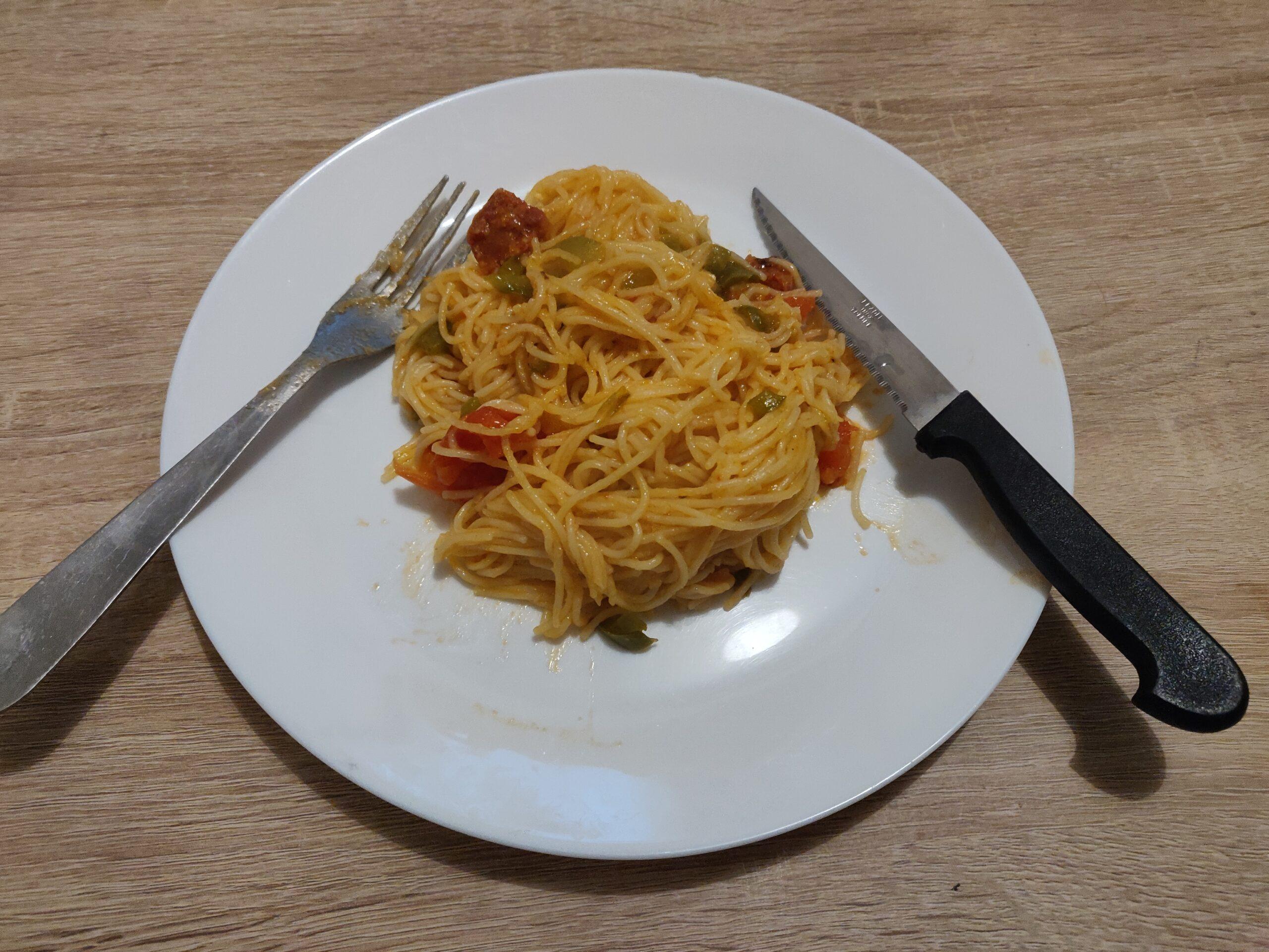 Au centre de l'image une assiette blanche, remplie de pâtes aux poivrons. Une fourchette est posée sur la gauche de la photo, un couteau, sur la droite.