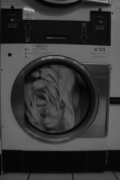 Une sécheuse en route qui brasse du linge. L'image est en noir et blanc.