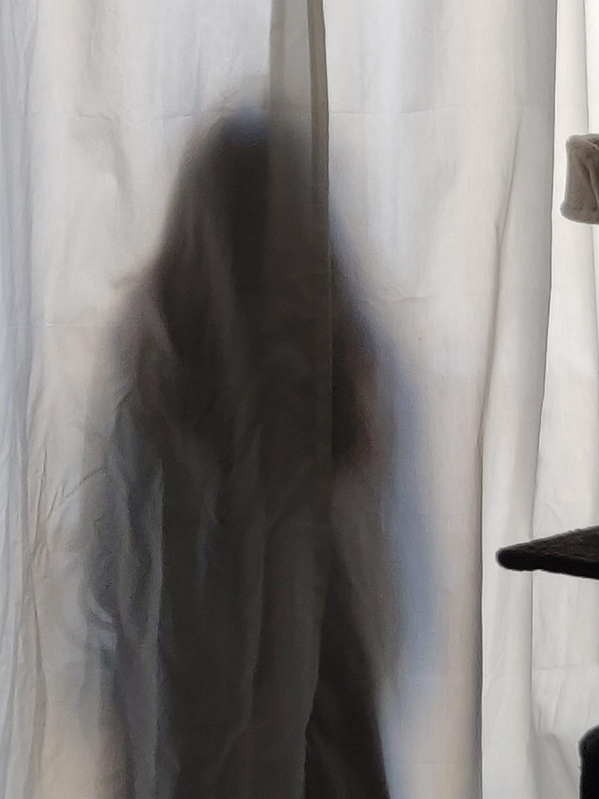 Une silhouette derrière des rideaux blancs.