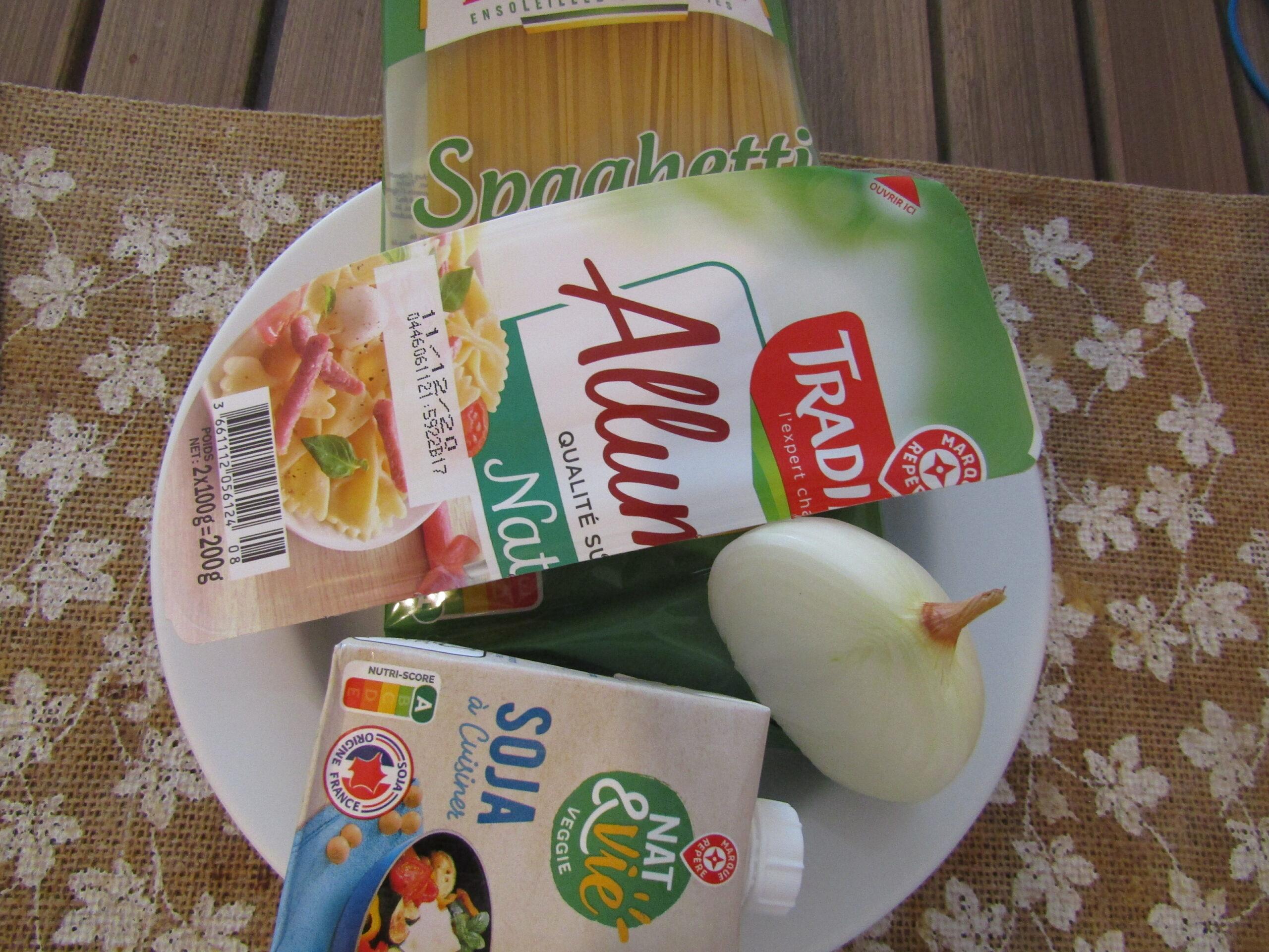 Plusieurs ingrédients dans une assiette : des lardons, un oignon, de la crème de soja et des pâtes (des spaghettis).