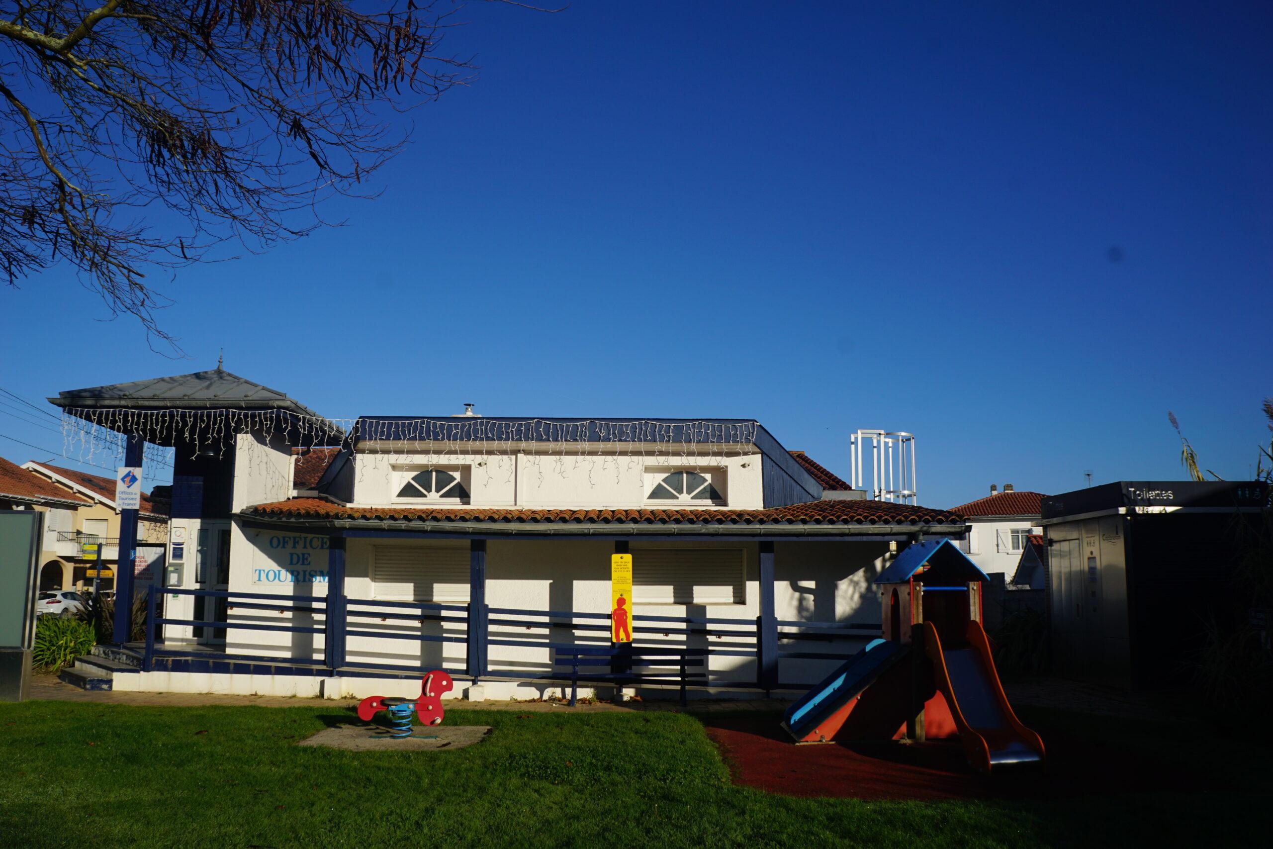 Photographie d'une aire de jeux pour enfants vide. Le ciel est bleu et dégagé.