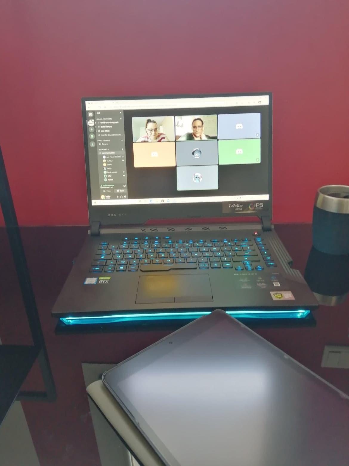 Photo d'un ordinateur portable noir posé sur un bureau noir. Sur l'écran de l'ordinateur on peut voir une réunion en visioconférence. C'est comme cela que les enseignements ont pu être maintenus à distance.