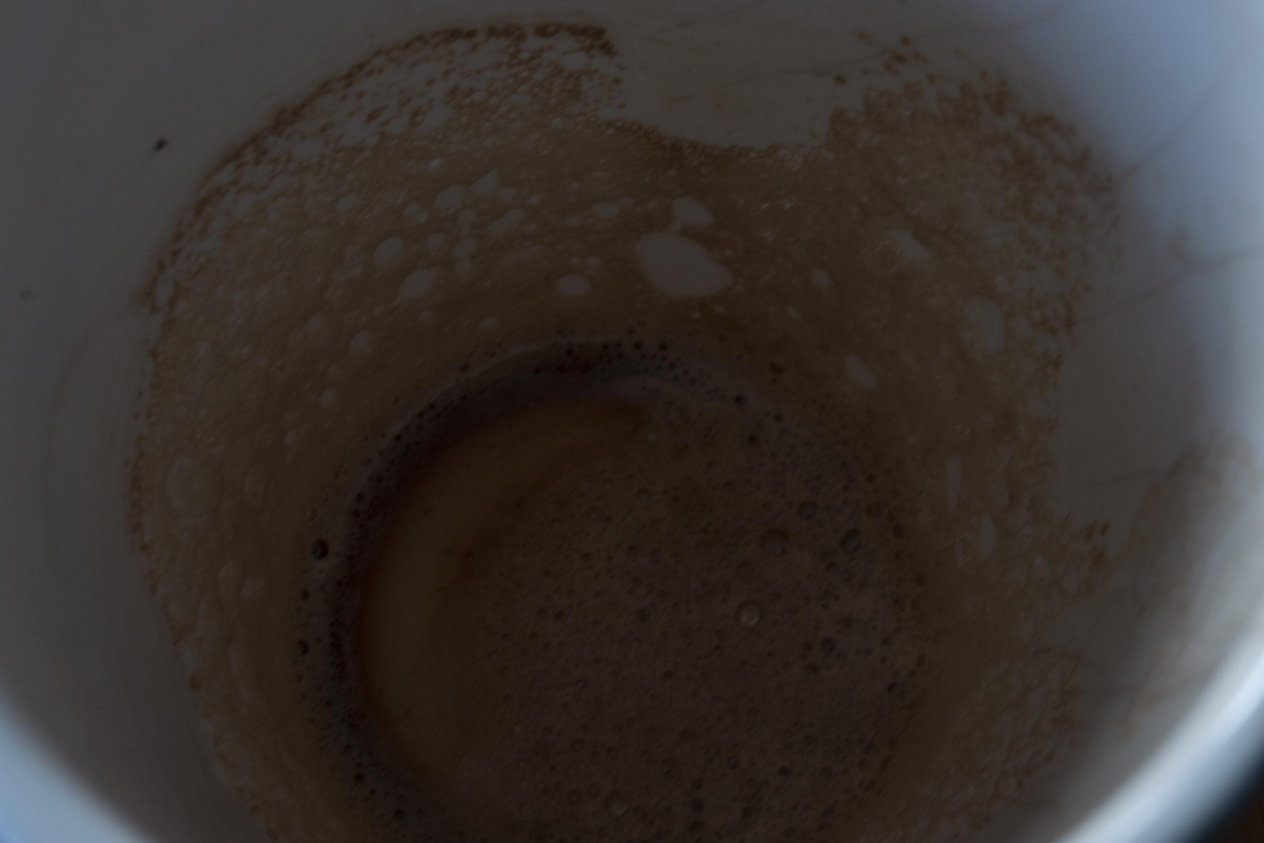 L'intérieur d'une tasse qui devait contenir du café. Les bords sont marrons dû à la trace de la mousse du café.