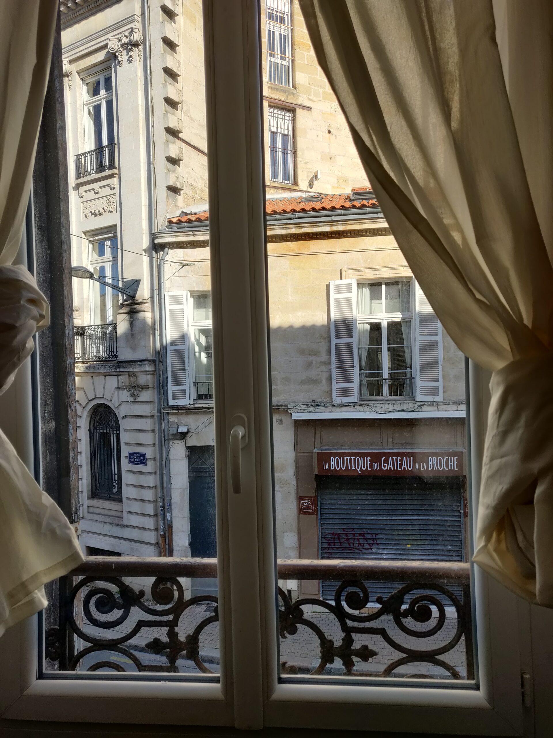 """Vue d'une fenêtre. Les rideaux de couleur blanc cassé sont noués. On aperçoit les bâtiments d'en face. Particulièrement """"la boutique du gâteau à la broche"""", rideau fermé, et orné d'un tag rouge."""