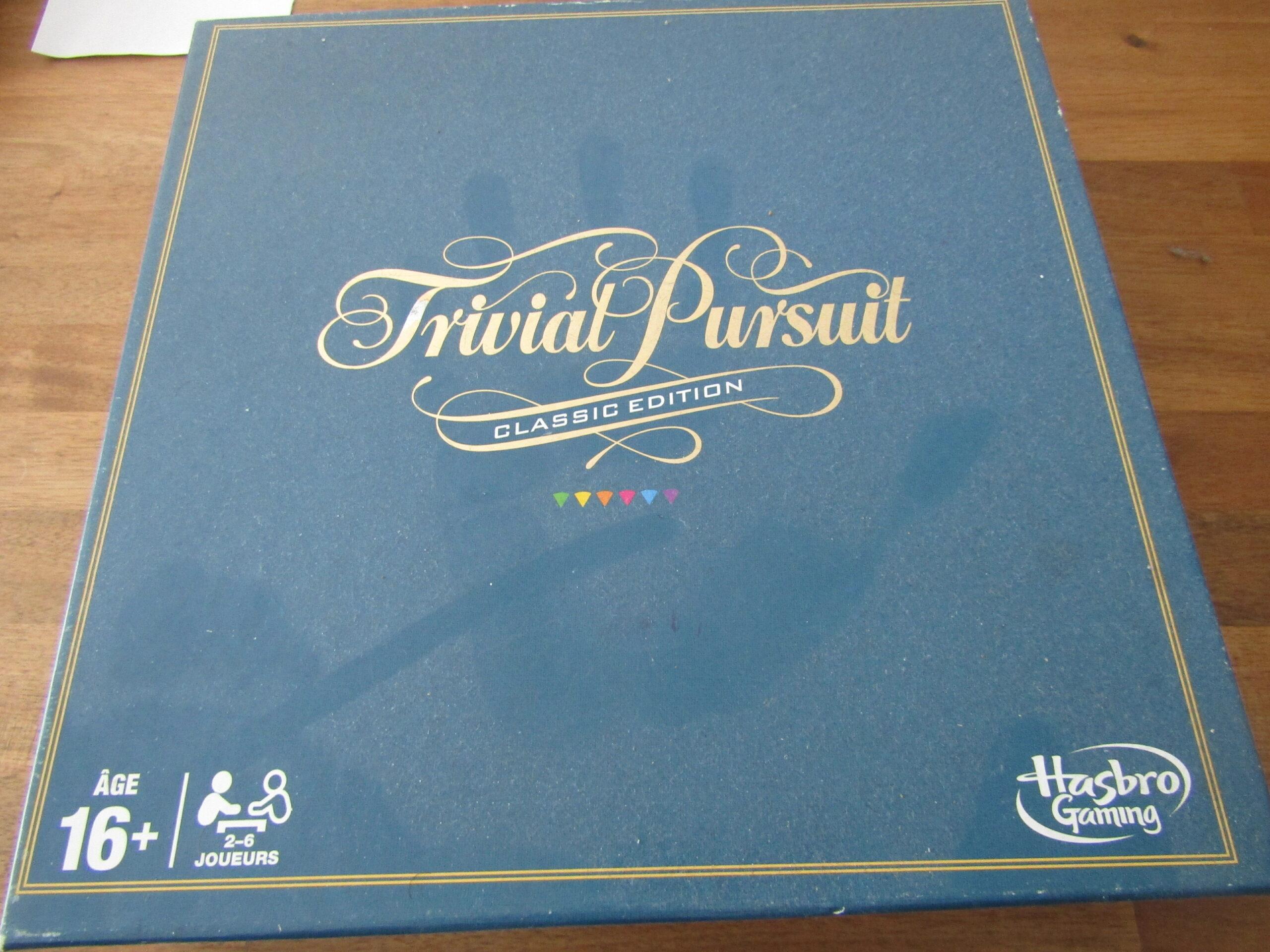 Un jeu de société Trivial Pursuit poussiéreux avec une trace de main sur le carton. Le carton est de couleur unie avec le nom du jeu par-dessus, au centre de la boîte.