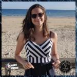 Portrait de Johanna Bermudes au bord de la plage. Elle a les cheveux longs et bruns. Elle porte des lunettes de soleil et sourit. Dans le coin bas gauche, le logo des Dealers de science, et en bas à droite, celui de l'Enquête des sens.