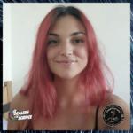 Portrait de Kimberly Bonnel, souriante, ses cheveux roses et longs encadrent son visage. Dans le coin bas gauche, le logo des Dealers de science, et en bas à droite, celui de l'Enquête des sens.