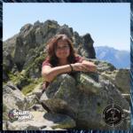 Clémence pose devant un paysage de montagne ensoleillé. Elle a les bras posés sur un rocher et sourit. Dans le coin bas gauche, le logo des Dealers de science, et en bas à droite, celui de l'Enquête des sens.