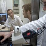 Serge Picaud et deux de ses collaborateurs, dans un laboratoire de recherche. Ils sont en train de parler, d'examiner des résultats devant un ordinateur et un microscope.