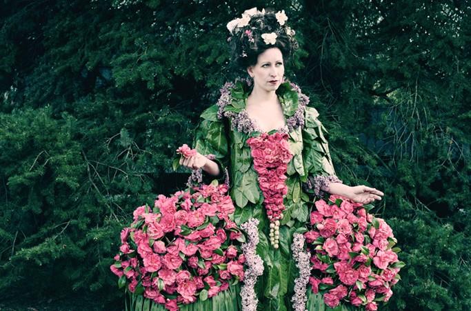 Photographie d'une personne portant une robe imposante et colorée, entièrement faite en fleurs et en feuilles. Le modèle porte aussi des fleurs dans les cheveux. Cette robe fait partie de la collection « Weedrobes ».