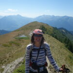 LIsl Weynans pose pour une photo. Elle est en randonnée dans la montagne. Elle porte une casquette et des lunettes. Elle sourit pour la caméra.