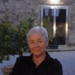 Portrait de Véronique Pallet tout sourire devant une maison de vacances et un beau citronnier.