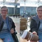 Photo d'une patiente privée de proprioception qui tient une tasse. Cette patiente est assise dans un fauteuil roulant, elle a des cheveux gris et courts et des lunettes rectangulaires noires. Elle est vêtue d'un T-shirt gris clair recouvert d'un gilet gris et noir. Elle possède également un sac bleu clair en bandoulière. Elle se trouve en extérieur à une table sur une terrasse, on aperçoit un bâtiment avec de grandes fenêtres dans le fond. Elle tient une tasse de café en carton marron dans la main droite le bras tendu, cette tasse est couverte par un couvercle en plastique blanc. La photo est séparée en deux moitiés droite et gauche. À gauche elle maintient sa tasse bien droite et elle la regarde, sa main se situe une trentaine de centimètres au dessus de la table. À droite elle ferme les yeux, son bras s'est abaissé et sa main frôle presque la table, la tasse penche vers la droite et est presque à l'horizontale.