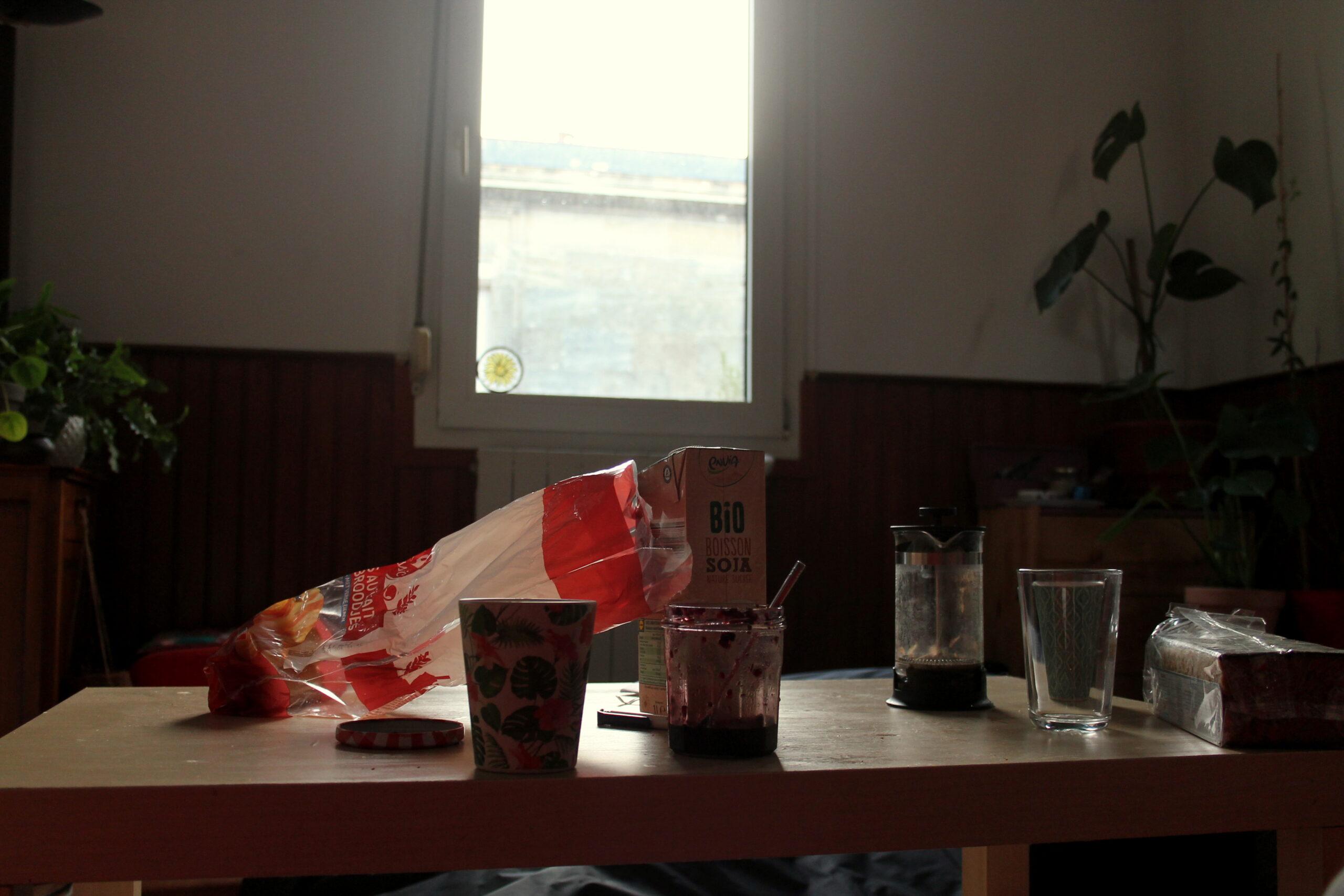 Nina prend son petit-déjeuner. Sur la table il y a du café de la confiture, du lait de soja et des petits pains au lait. En fond, une fenêtre avec les volets ouverts.