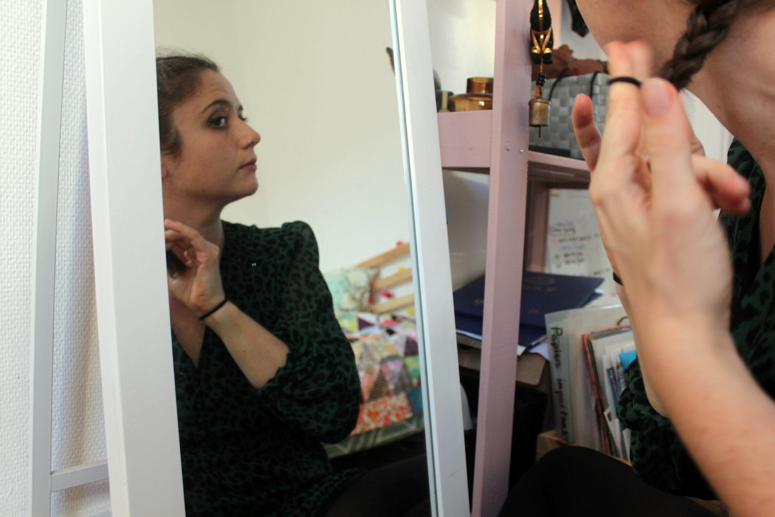 Nina se regarde dans le miroir pour se préparer. Elle se coiffe en se faisant des tresses.