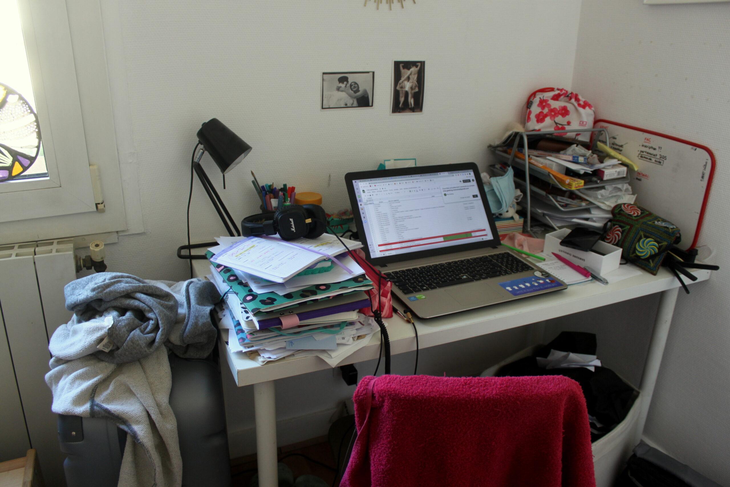 Le bureau de Nina. Il est très désorganisé. Un ordinateur allumé est au milieu. Il est entouré de nombreux papiers, cahiers et objets.