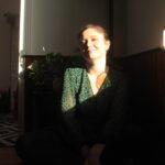 Nina est assise proche de sa fenêtre. Le soleil arrive directement sur son visage. Elle est souriante et regarde la caméra.