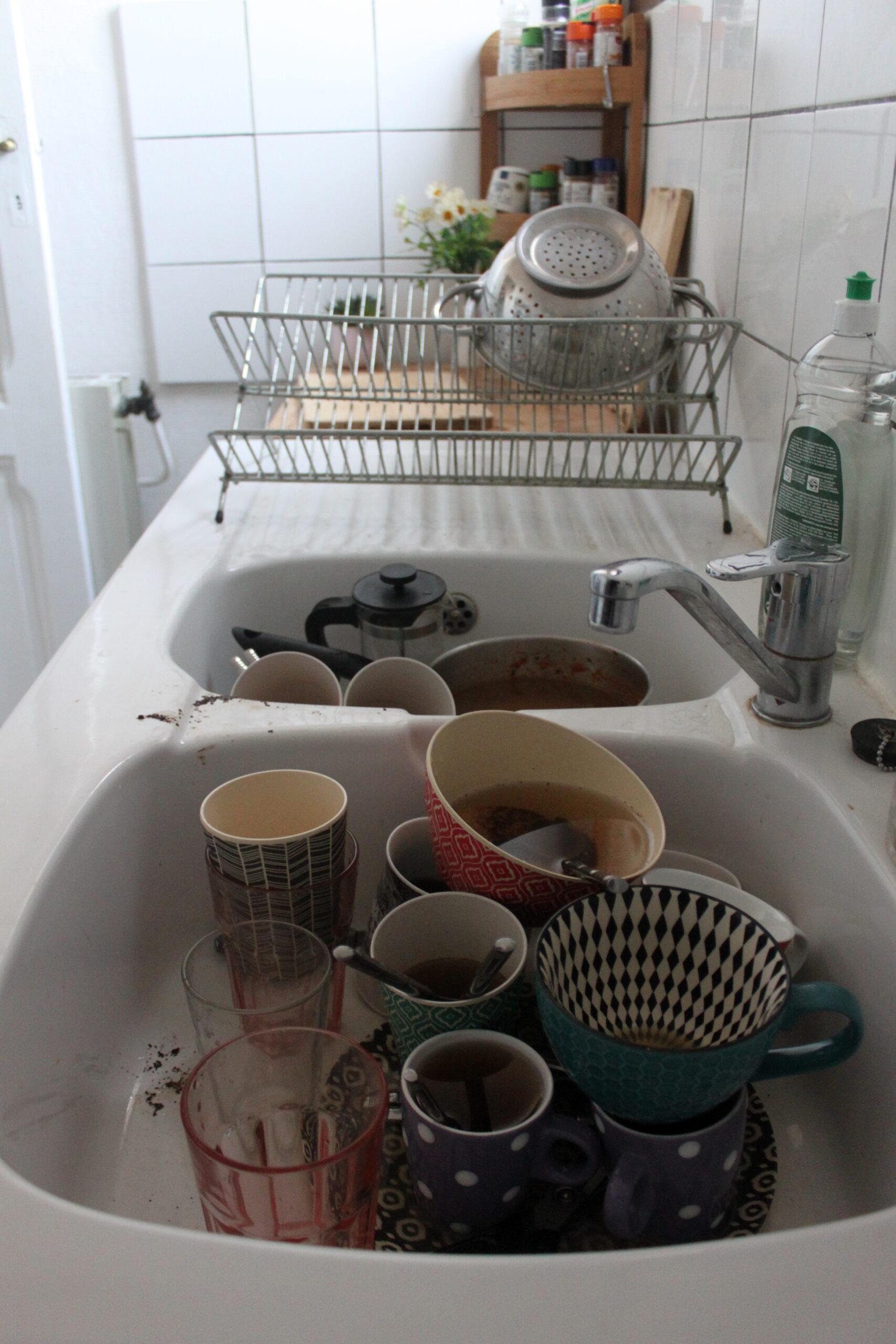 Une pile de vaisselle est dans l'évier de la cuisine. Principalement des tasses car Nina boit beaucoup de café.