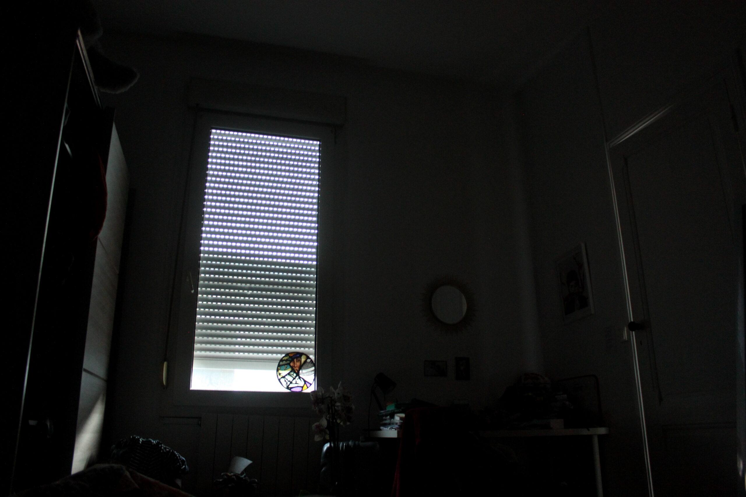 Une nouvelle journée, toujours la même vue depuis le lit. Cette fois-ci on remarque également la porte de la chambre. Le volet est à peine plus levé que la première fois.