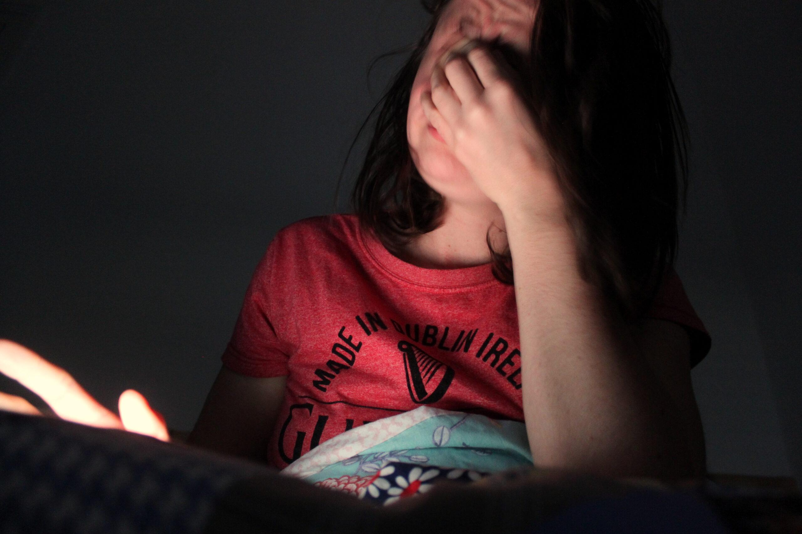 De nouveau, Nina regarde son téléphone au réveil. Ce dernier est la seule source lumineuse.