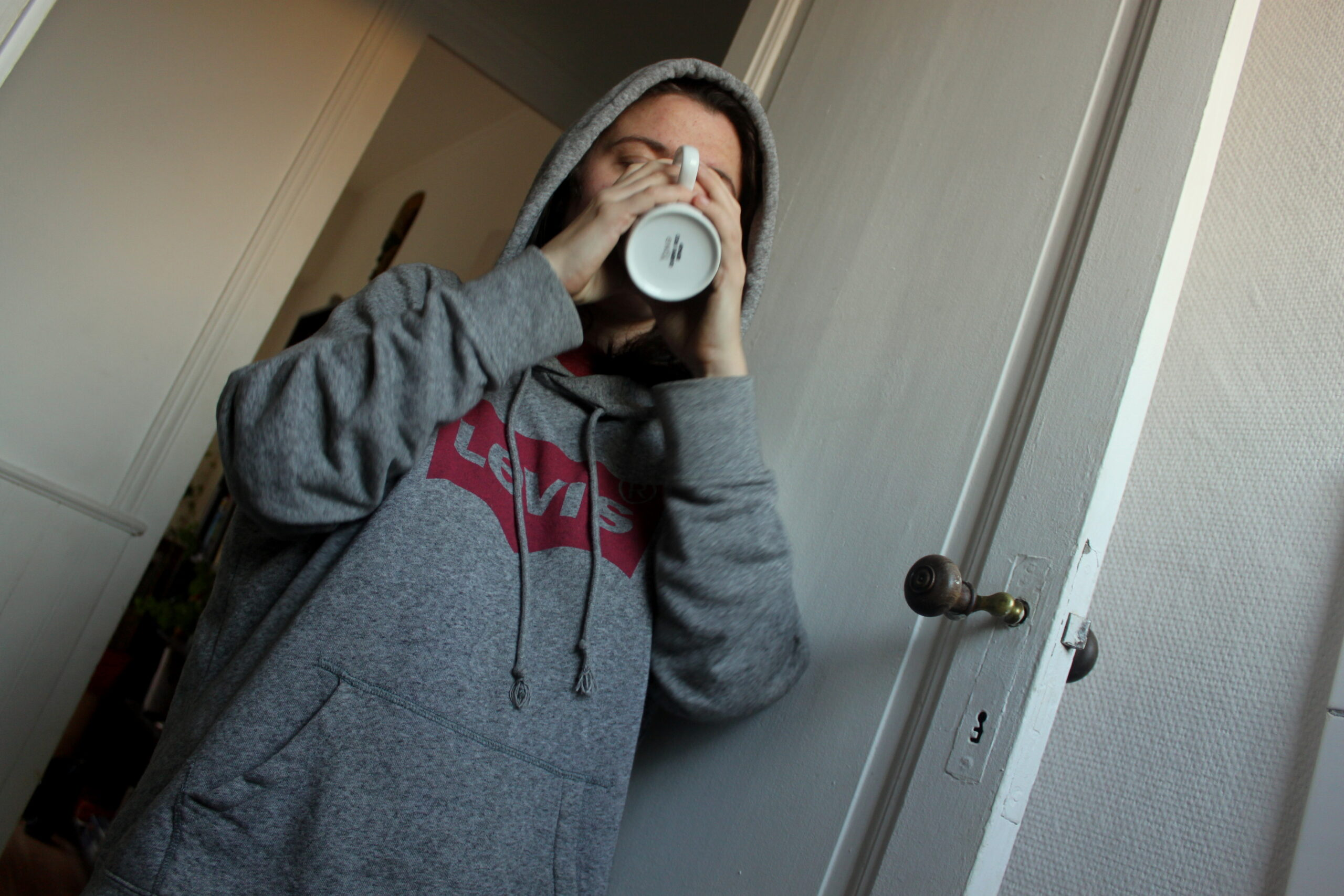 Nina boit un café et porte un pull. Elle est dans sa cuisine, à côté d'une porte.