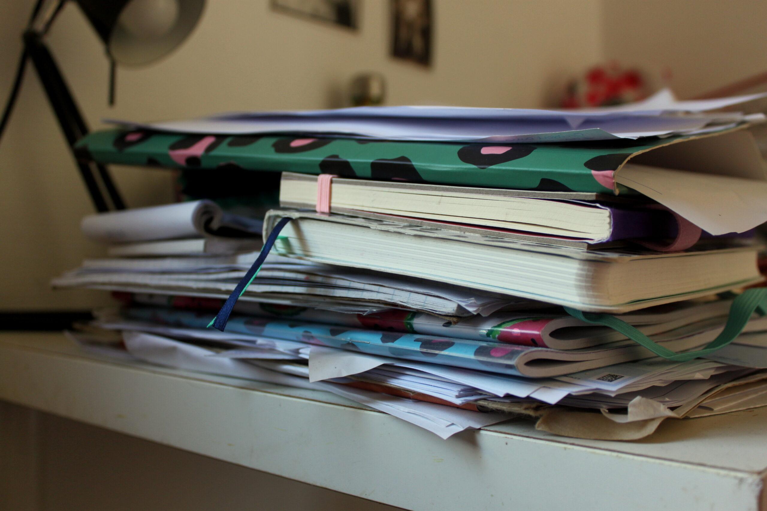Le bureau de Nina vu de très proche. On voit un tas de cahiers et de feuilles.