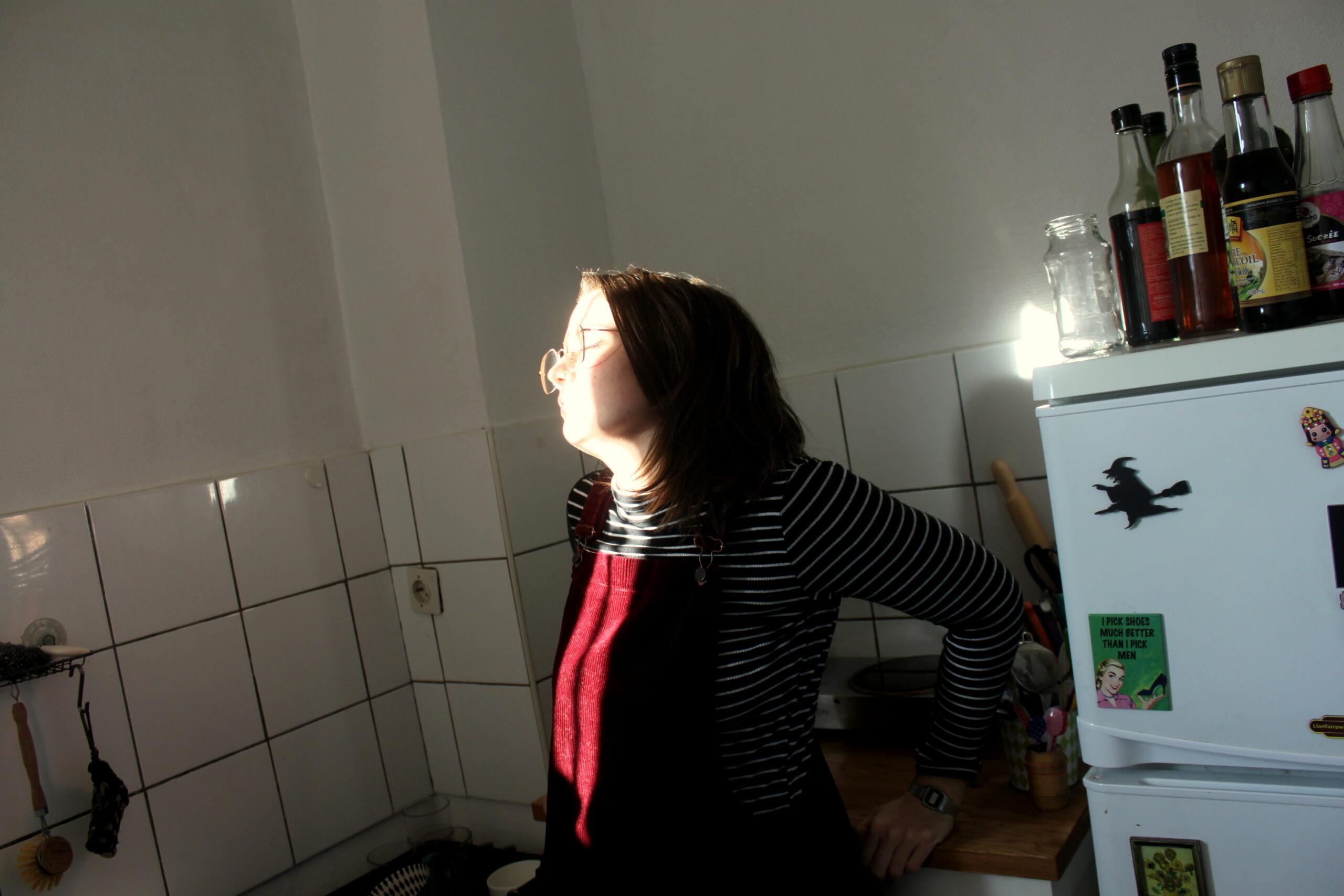 Nina prend le soleil dans sa cuisine, adossée sur un meuble. C'est une petite pause qu'elle s'accorde dans la journée.