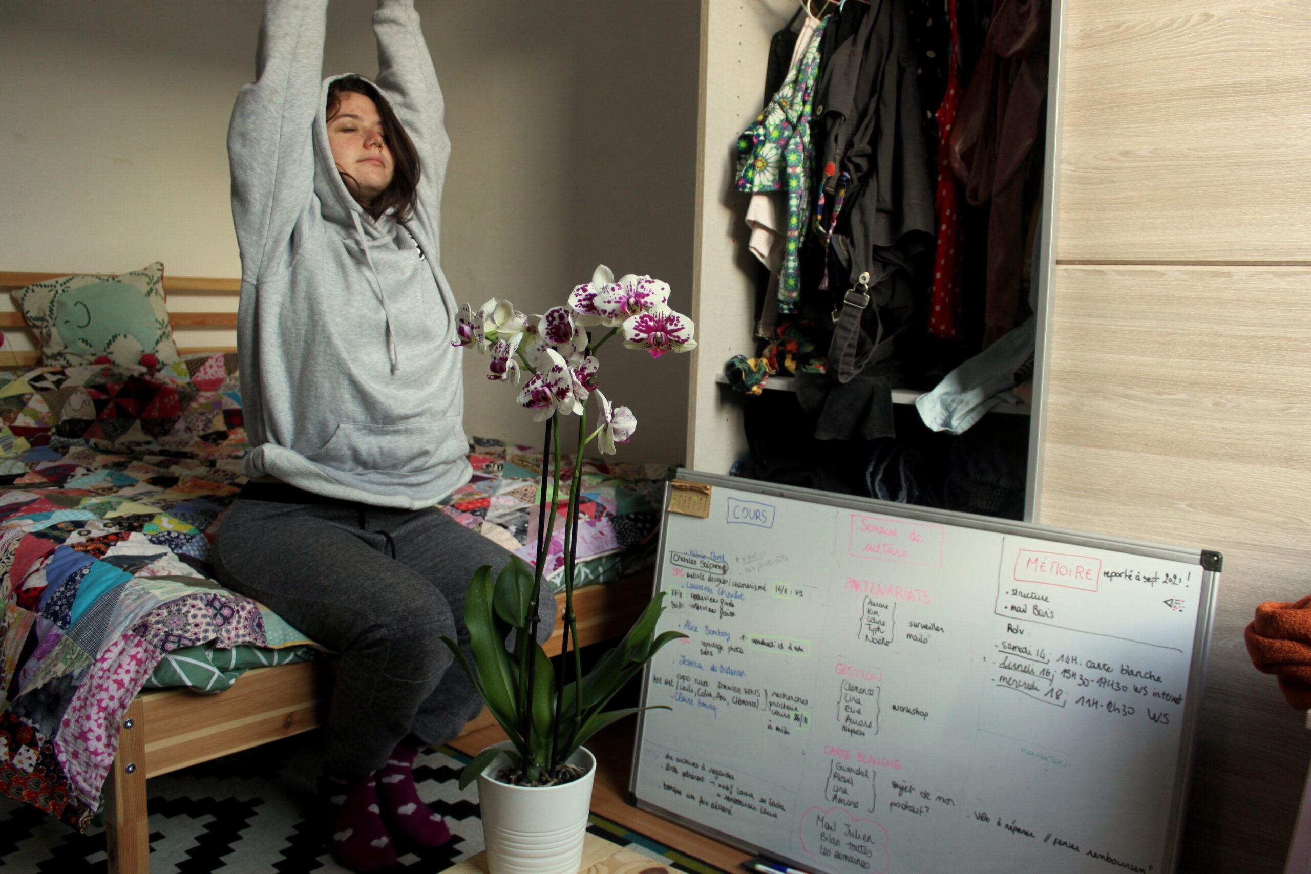 Nina est assise sur son lit elle s'étire. À côté d'elle, il y a un tableau avec toutes ses listes de choses à faire pour l'université. Au milieu de la pièce il y a une orchidée.