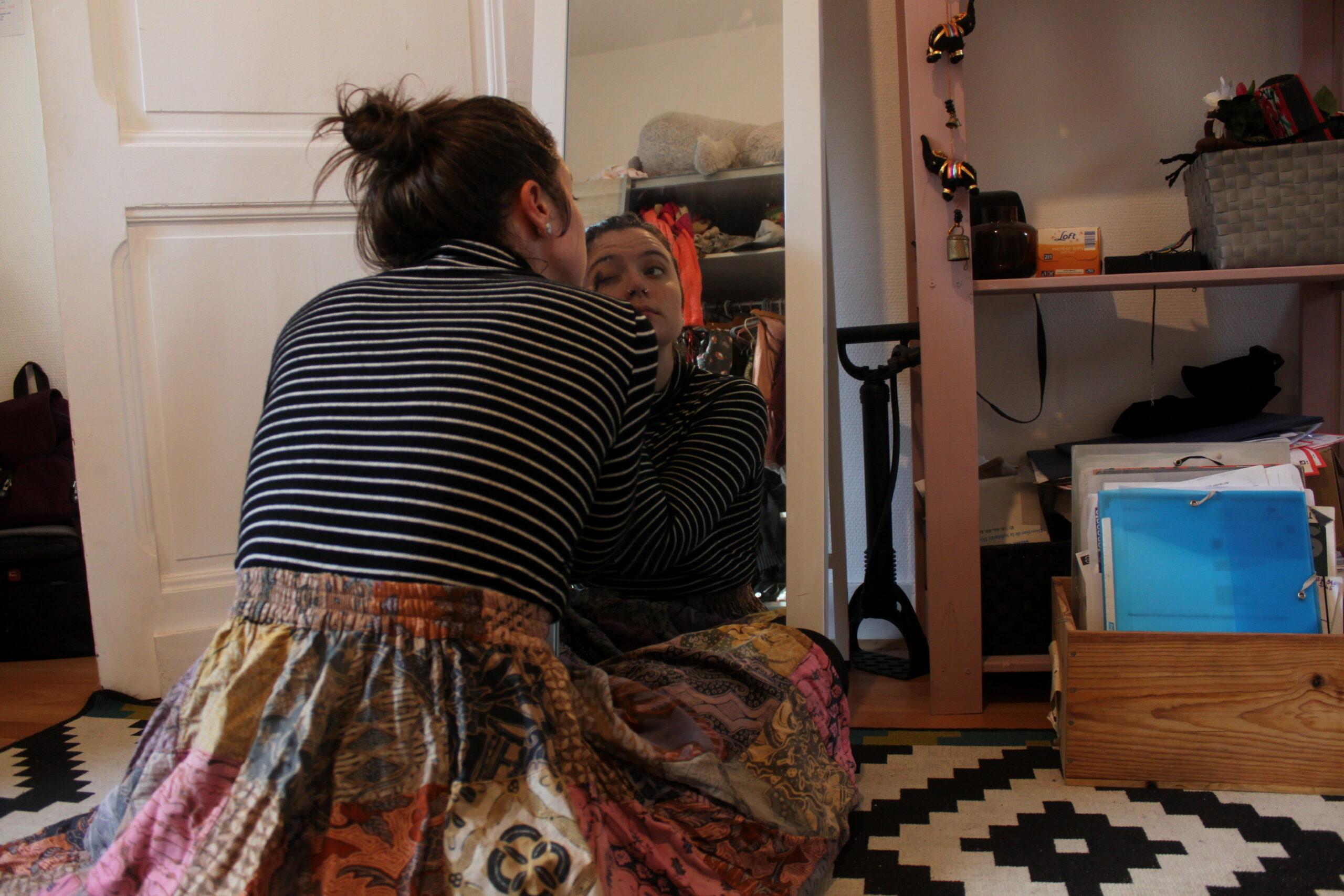 Nina est devant son miroir. Elle se maquille.