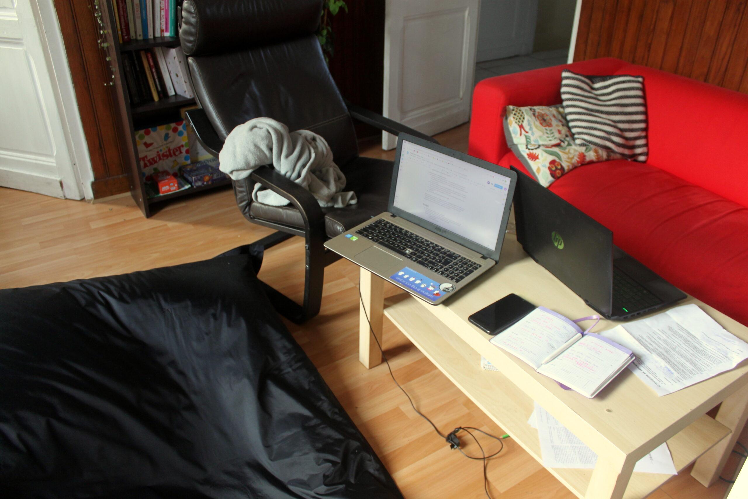 Le salon est devenu le bureau pour la journée. Sur la table basse il y a deux ordinateurs et un cahier.