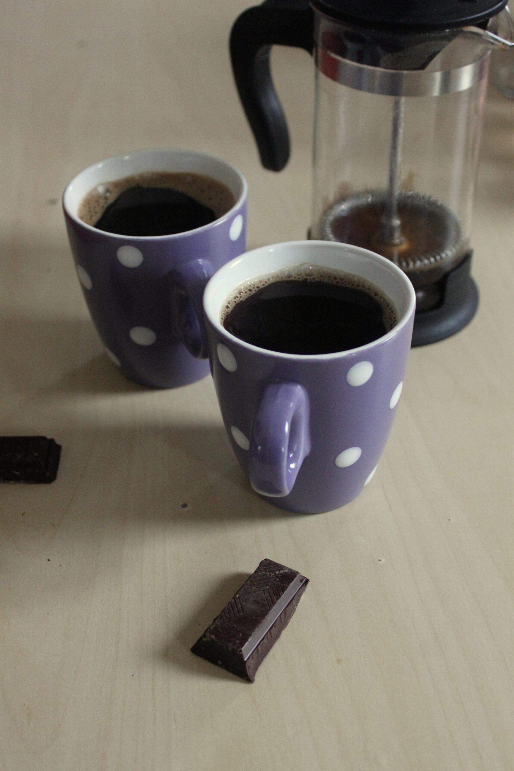 Une petite pause ! Photo zoomée de deux cafés et deux carrés de chocolat.