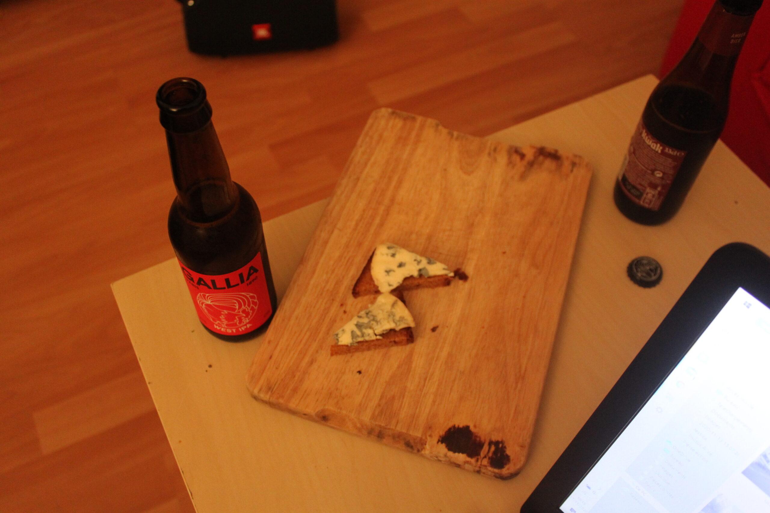 Fin de journée : sur un plateau il y a du fromage et à côté deux bières.