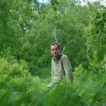 Charles Stépanoff est assis dans une forêt verte. Il regarde l'objectif et est serein.