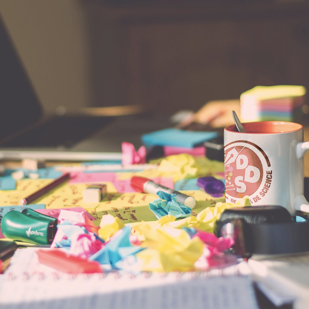 Image avec tasse dans un casque audio à droite, des papiers multicolores au centre et un pc ouvert en arrière plan flouté à gauche