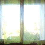 Photographie de la fenêtre de Nathan Florent avec des rideaux et la fenêtre fermée.