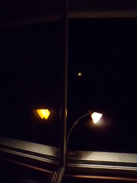 Photographie de la fenêtre de Nathan Florent avec sa lampe de bureau reflétée dans la vitre, de nuit.