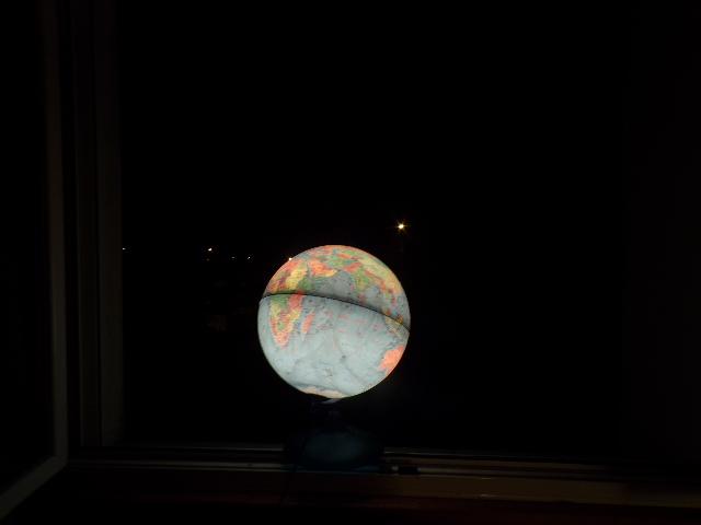Phographie de la fenêtre de Nathan Florent avec son globe lumineux, de nuit.