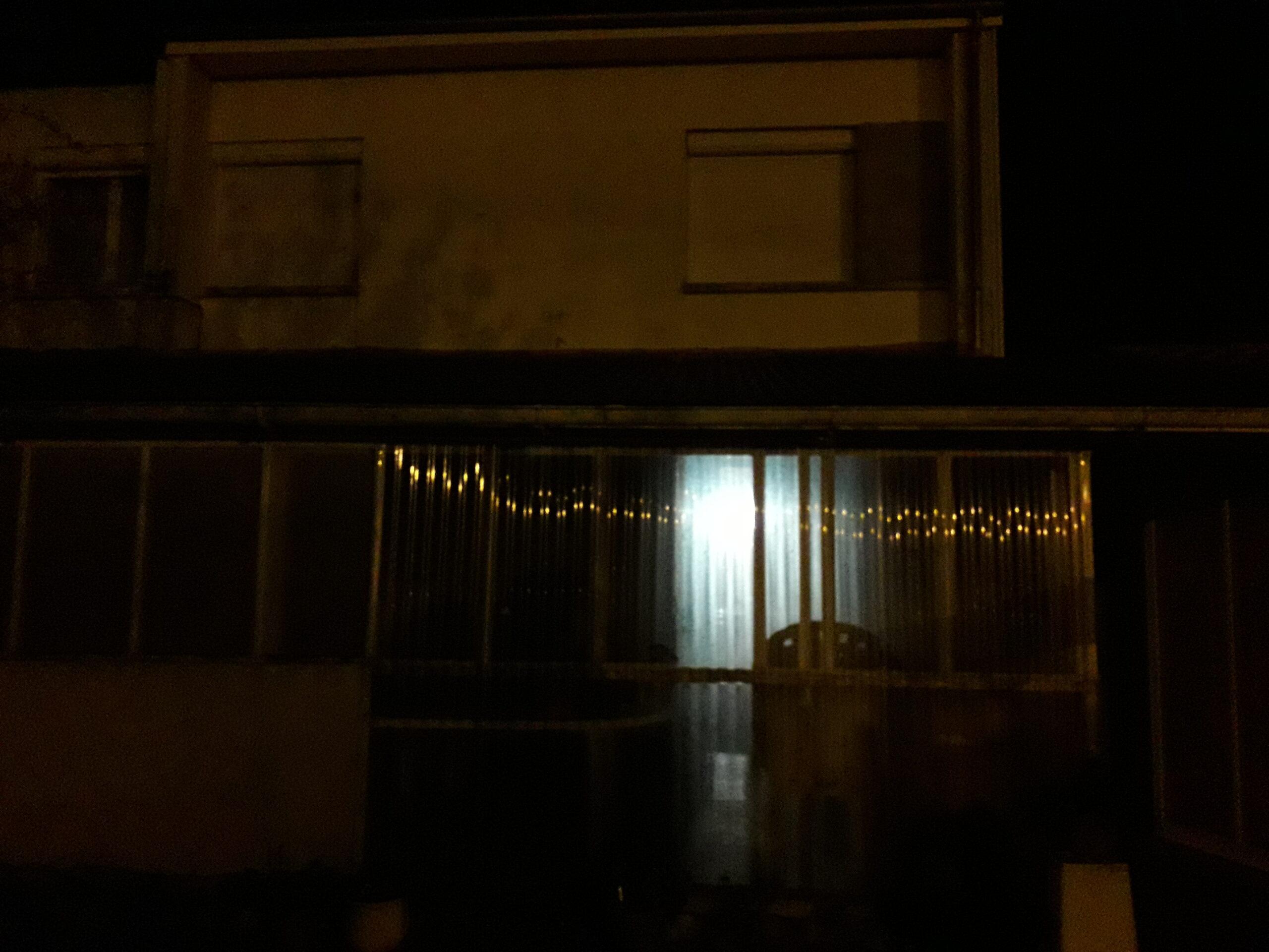 Photographie de la véranda de Nathan Florent de nuit avec les reflets des lampadaires.