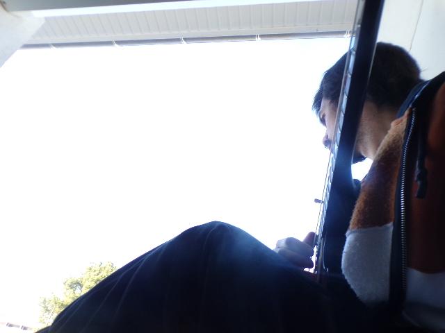 Selfie en contre-plongée de Nathan Florent avec sa guitare (Gibson Les Paul) sur le rebord de sa fenêtre, en pleine journée.