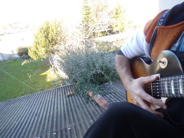 Selfie de Nathan Florent avec sa guitare (Gibson Les Paul) sur le rebord de sa fenêtre, de jour.