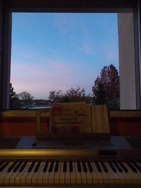 Photographie de la fenêtre de Nathan Florent le soir avec un synthétiseur et un journal.