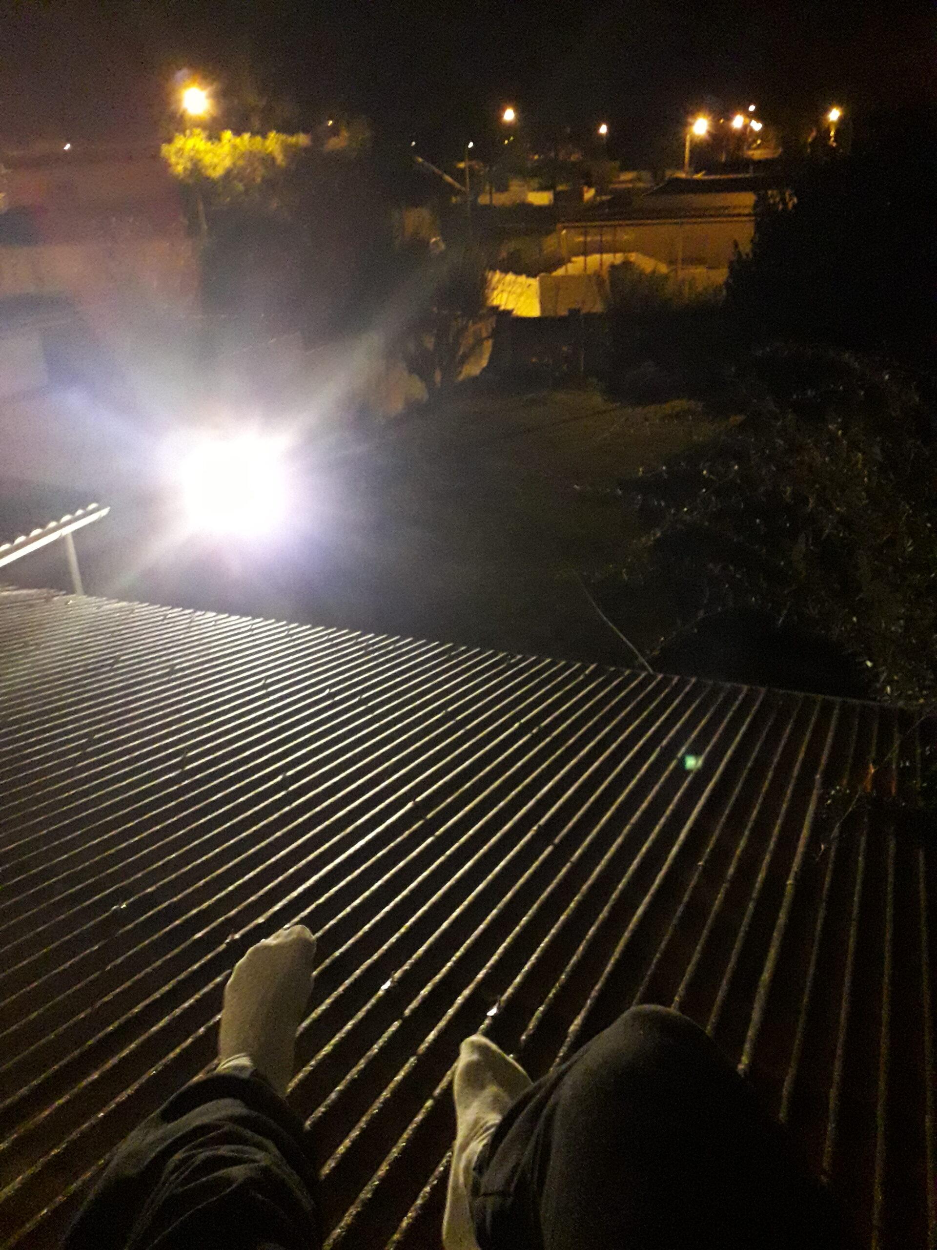 Photographie du jardin de Nathan Florent depuis le rebord de sa fenêtre de nuit, les jambes dans le vide.